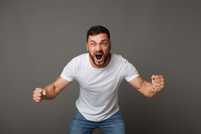 Junges verärgertes hübsches muskulöses Mannschreien laut stockfotografie