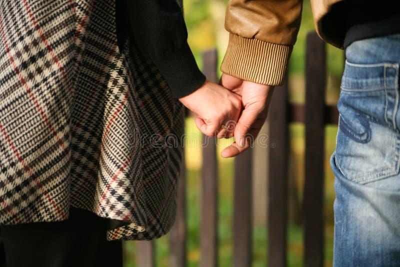 Junges verheiratetes Paar, das Hände anhält stockbilder
