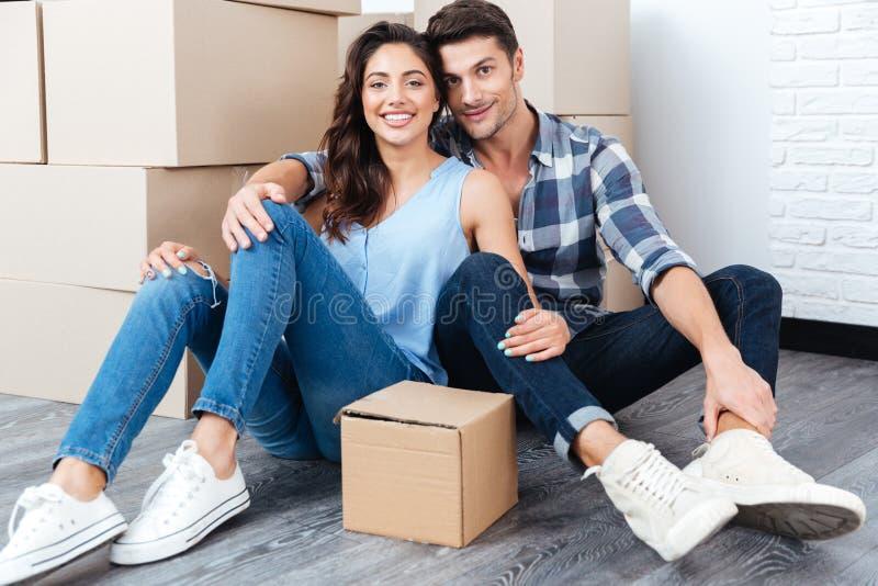 Junges verheiratetes Paar, das in ihrem neuen Haus sitzt lizenzfreie stockfotografie