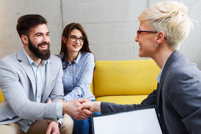 Junges verheiratetes Paar an ihrem Berater, an Ratgeber oder an Vertreter lizenzfreies stockfoto
