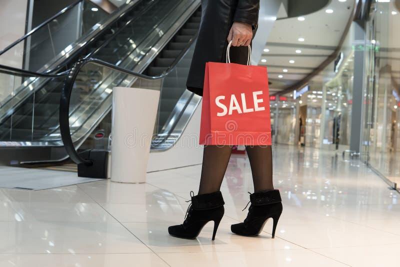 Junges vornehmes modernes Mädchen geht zu einem großen Bekleidungsgeschäft mit Einkaufstaschen Der Aufschriftverkauf auf der rote lizenzfreie stockbilder