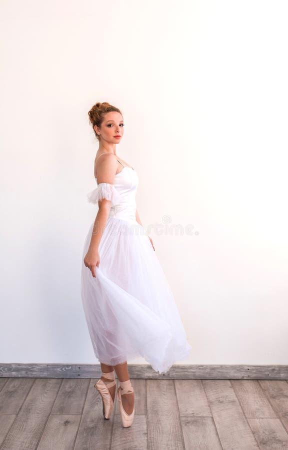 Junges würdevolles Ballerinatanzen auf weißem Studio lizenzfreies stockfoto