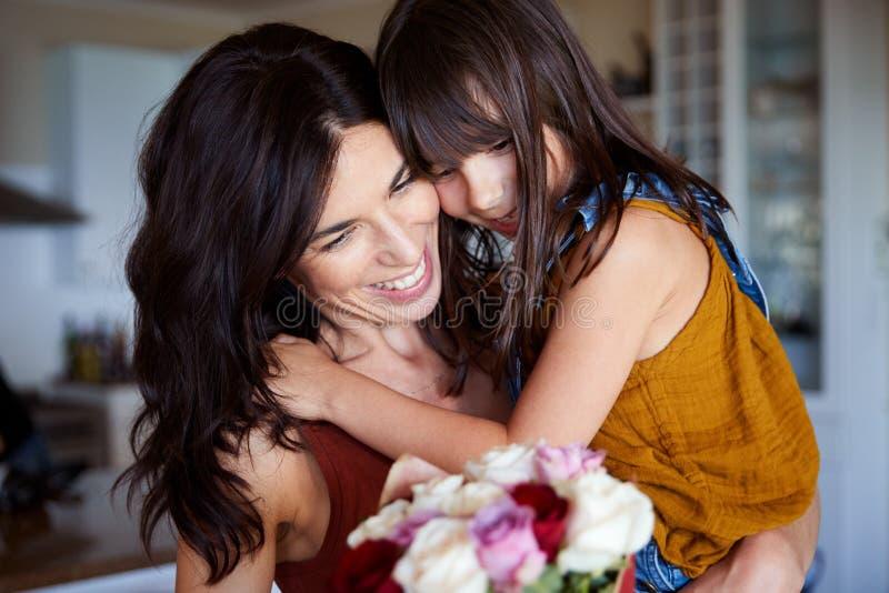 Junges weißes Mädchen, das ihrer Mutter Blumen als Geschenk an Mother?s-Tag, Abschluss aufgibt lizenzfreies stockbild