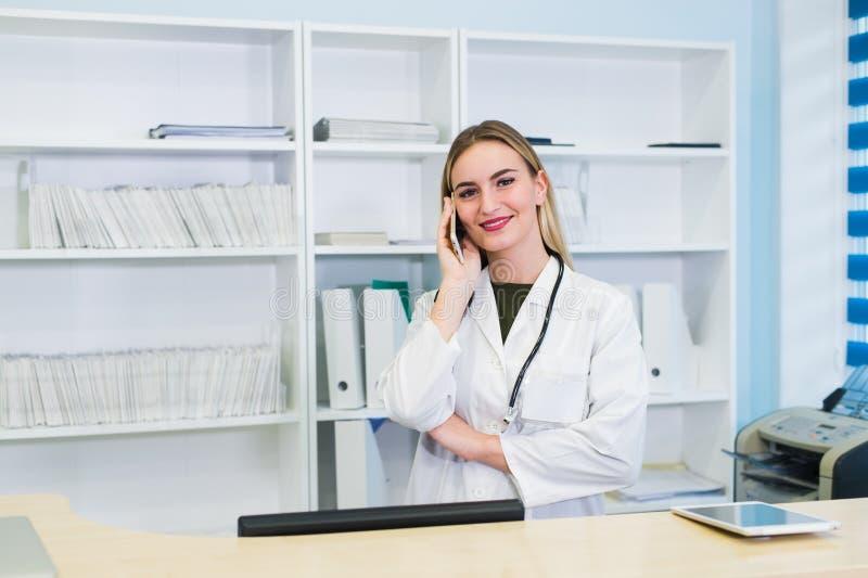 Junges weibliches Empfangsdame talkingto der Kundenpatient im Krankenhaus stockfotos