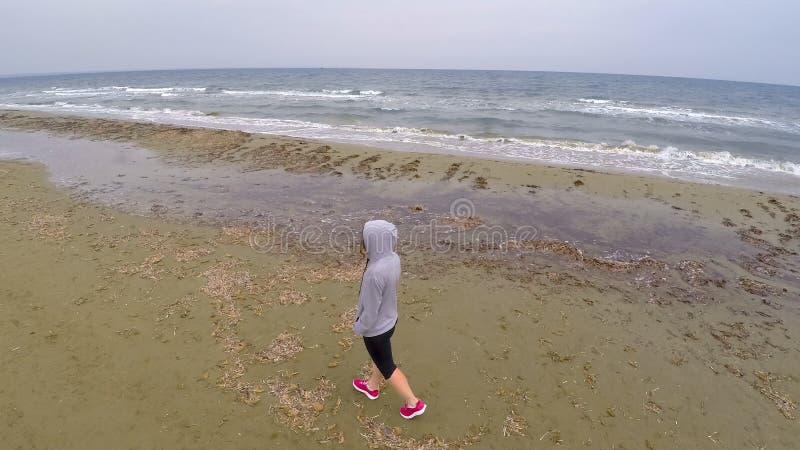 Junges weibliches Gehen auf den Strand und Denken an das Leben, Luftbrummenschuß lizenzfreie stockfotografie