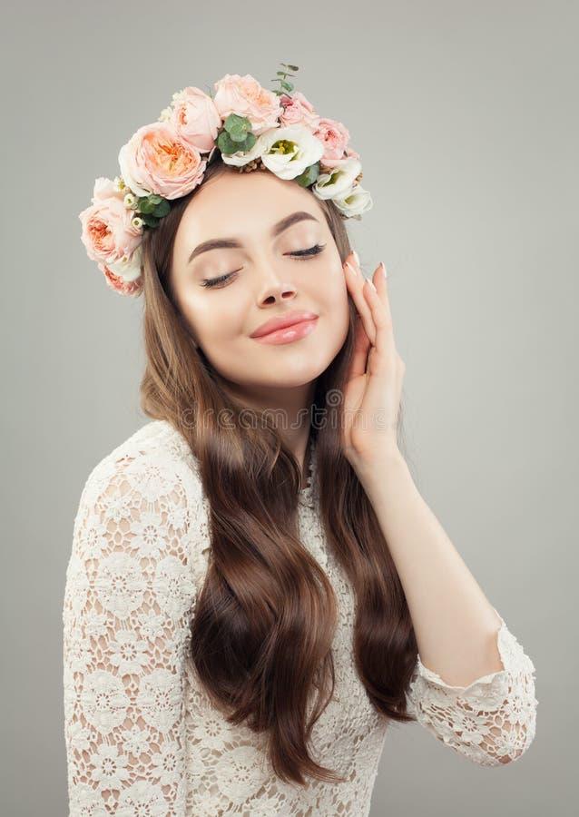 Junges weibliches Gesicht Hübsche Frau mit klarer Haut und rosafarbenem Blumenporträt stockfoto