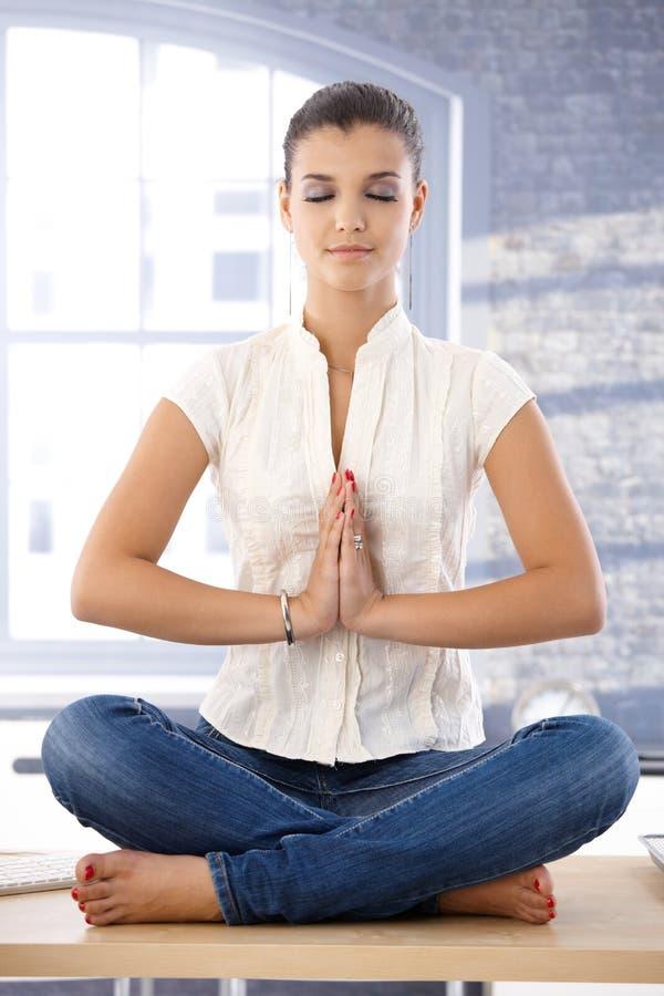 Junges weibliches Meditieren auf Schreibtisch lizenzfreies stockbild