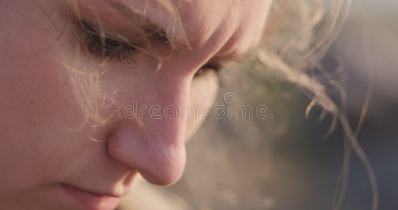 Junges weibliches Nahaufnahmeporträt, das auf einer Küste mit durchdachtem Blick sitzt lizenzfreie stockfotografie