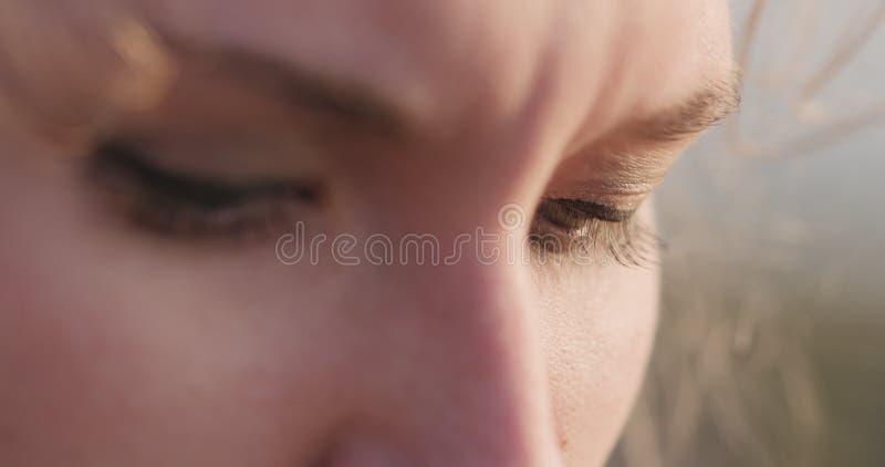 Junges weibliches Nahaufnahmeporträt, das auf einer Küste mit durchdachtem Blick sitzt stockfotografie