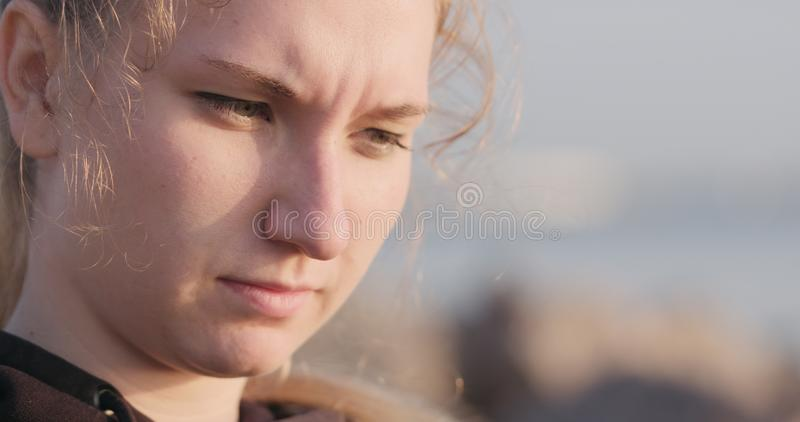 Junges weibliches Nahaufnahmeporträt, das auf einer Küste mit durchdachtem Blick sitzt lizenzfreie stockfotos