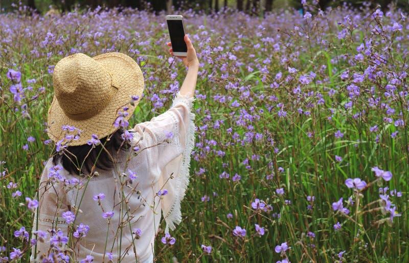 Junges weibliches nehmendes selfie Bild auf dem Blumengebiet mit ihrem intelligenten Mobiltelefon stockbilder