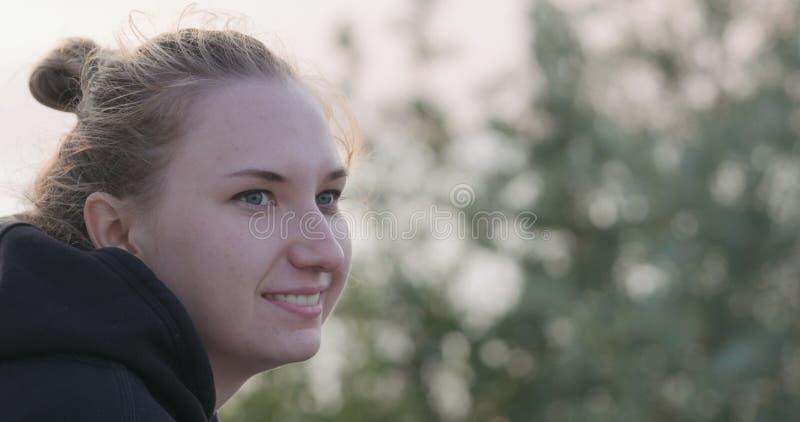 Junges weibliches Porträt, das auf einer Küste mit durchdachtem Blick sitzt stockbilder