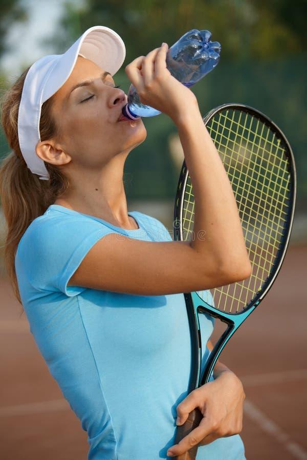 Junges weibliches Trinkwasser des Tennisspielers lizenzfreies stockbild