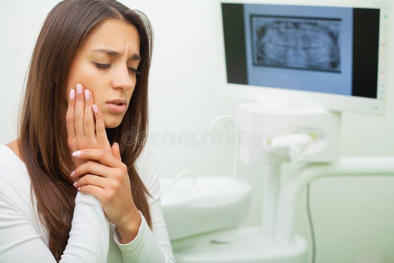 Junges weibliches, Zahnschmerzen habend Umgekippte Frau an den Pulsierungsschmerz Zahnarzt Constant stockfotografie