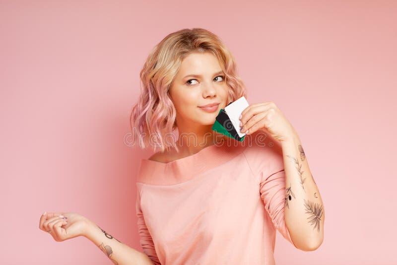 Jungfrau der Jungfrau mit farbigen Haaren und Tätowierungen, die Kreditkarten besitzen Erwerb von Konzepten Rosa stockbilder