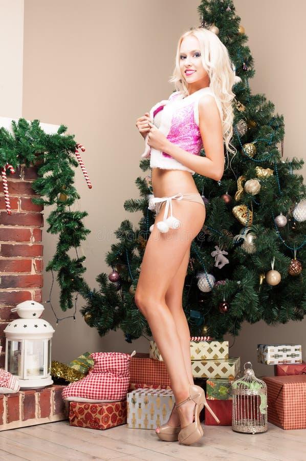 Jungfru- sexig ung kvinna för härlig blond snö i en rosa dräkt och på tegelstenspisen, långa härliga ben i höga häl Nytt år, arkivfoto