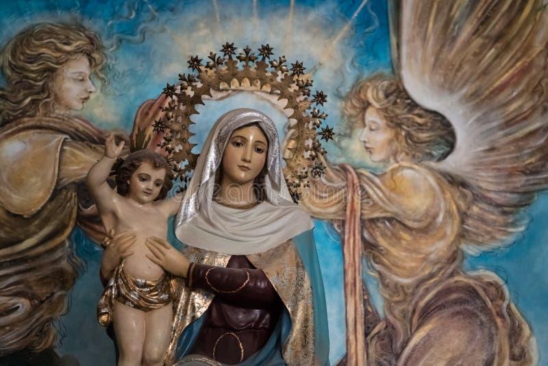 Jungfruliga Mary med barnet Jesus och målade änglar arkivbild