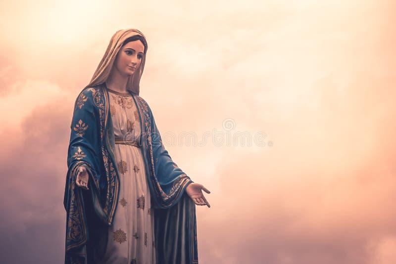 Jungfruliga Mary staty på katolska kyrkan med solljus i molnig dagbakgrund arkivbild