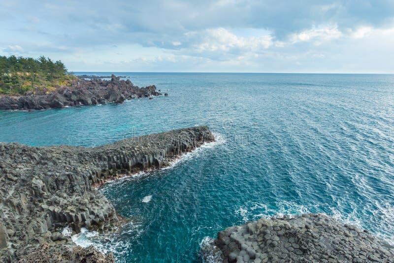 Jungmun Daepo kust med columnar skarvar på Jeju ö, södra K royaltyfri fotografi