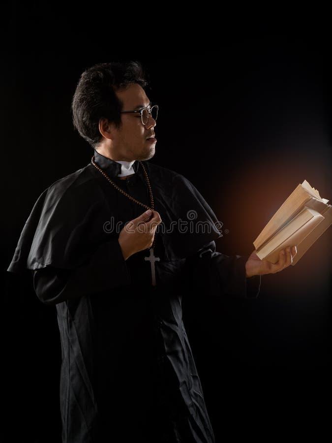JungPriester mit Gläsern, die alte Bibel halten und beten stockbild