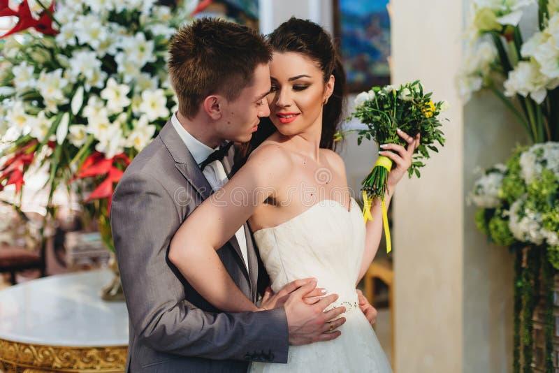 Jungvermählten, die auf dem Hintergrund von Blumen umfassen lizenzfreie stockbilder