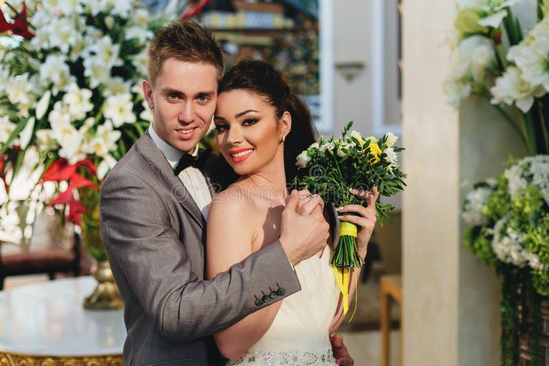 Jungvermählten, die auf dem Hintergrund von Blumen umfassen lizenzfreie stockfotos