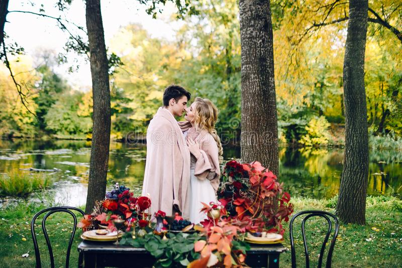 Jungvermählten, die unter dem Plaid nahe bei der festlichen Tabelle küssen Braut und Bräutigam im Park Herbsthochzeit gestaltungs lizenzfreie stockfotografie