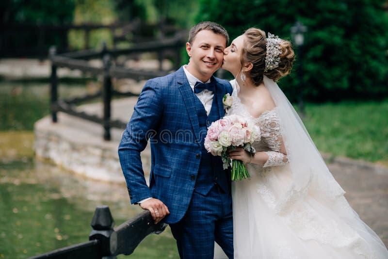 Jungvermählten gehen in den grünen Park Der Mann haftete dem Zaun an und umarmt seine Frau, das Mädchen küsst ihre Liebe lizenzfreies stockfoto
