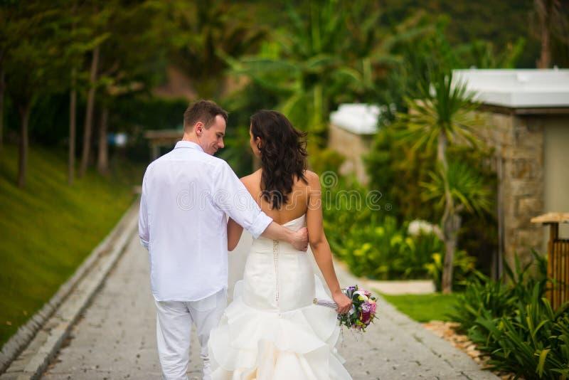 Jungvermählten gehen in den Park in den Tropen lizenzfreie stockbilder