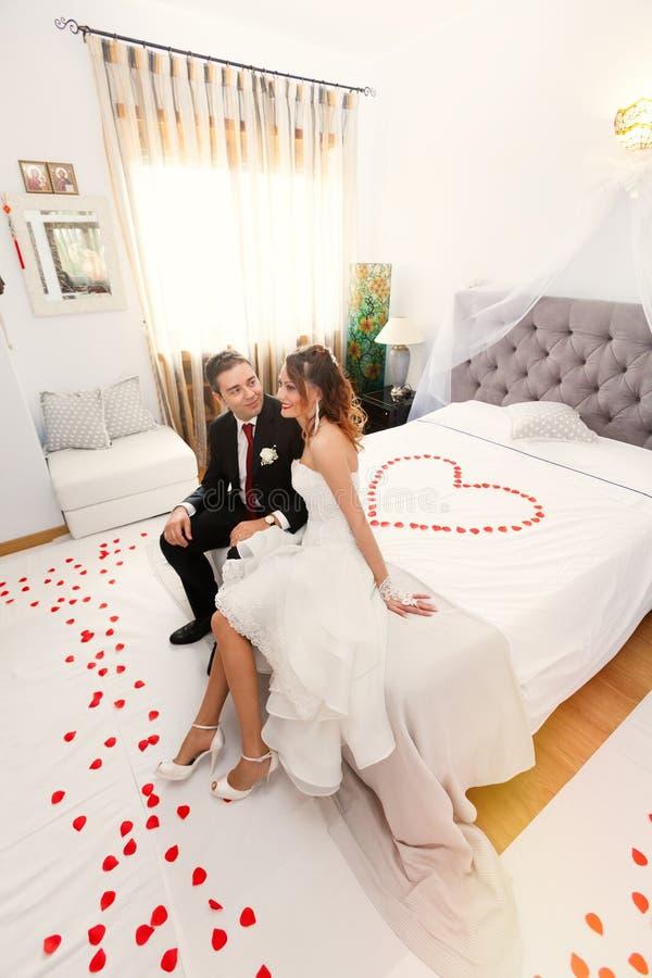 Jungvermählten im Schlafzimmer mit Herzen lizenzfreie stockfotos
