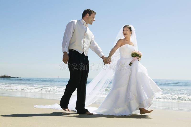 Jungvermählten-Paar-Händchenhalten beim Gehen auf Strand lizenzfreies stockbild