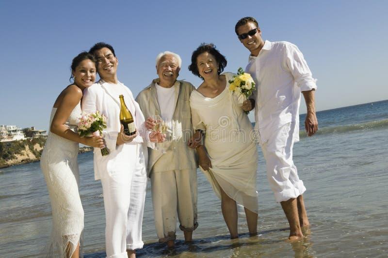 Jungvermählten-Paare mit den Hochzeits-Gästen, die auf Strand feiern stockbild