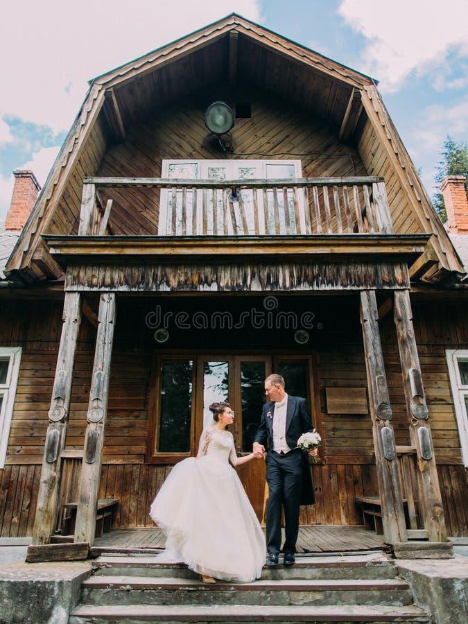 Jungvermählten sind Händchenhalten beim Hinuntergehen die Treppe des alten Waldhauses lizenzfreie stockfotos