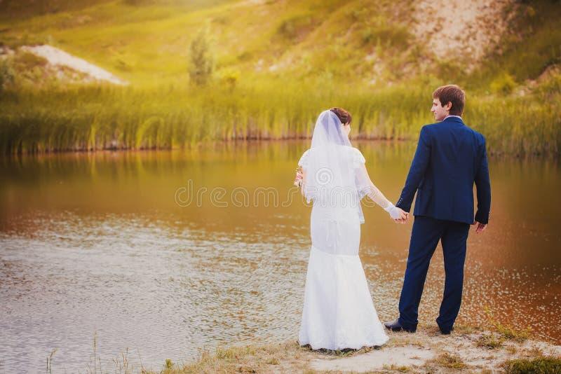 Jungvermählten umarmen im grünen Park lizenzfreies stockfoto