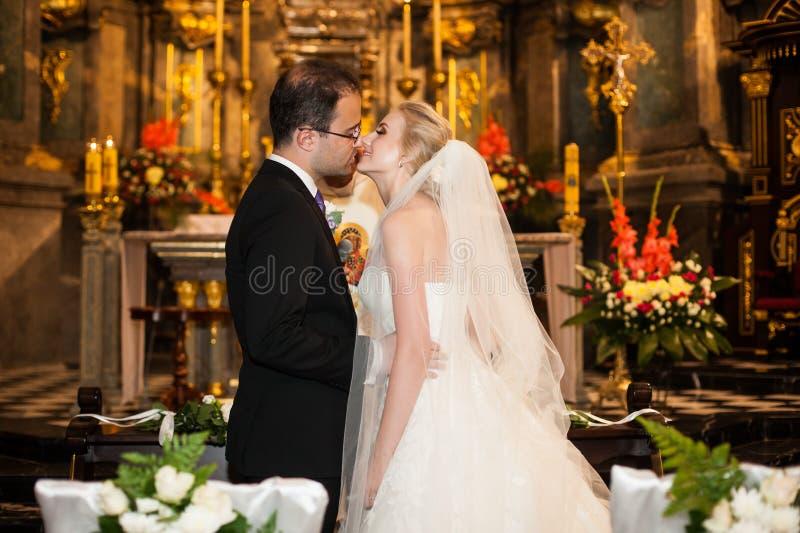 Jungvermähltenbraut und -bräutigam küssen zuerst an der Hochzeitszeremonie im churc stockfotos