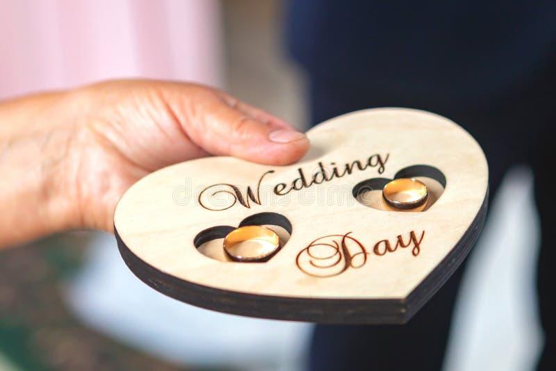 Jungvermählteneheringe auf einem hölzernen Herz-förmigen Stand in der Kirche stockbild