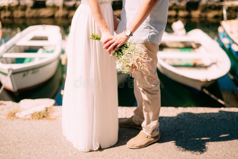 Jungvermähltengriffhände auf dem Meer Verbinden Sie Holdinghände Heiratsi lizenzfreies stockbild