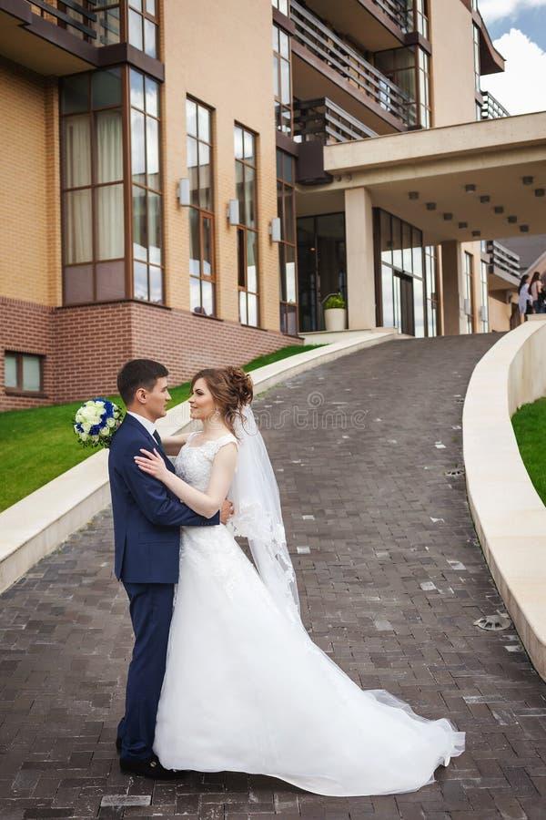 Jungvermähltenpaare, die auf dem Weg gegen Architektur der Stadt umarmen und küssen stockbilder