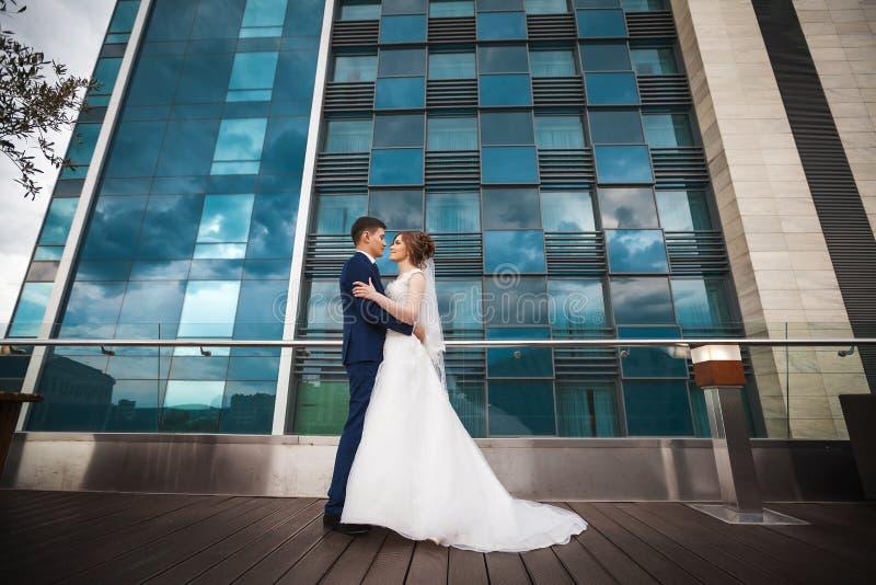 Jungvermähltenpaare, die gegen Luxusrestaurant umarmen lizenzfreies stockfoto