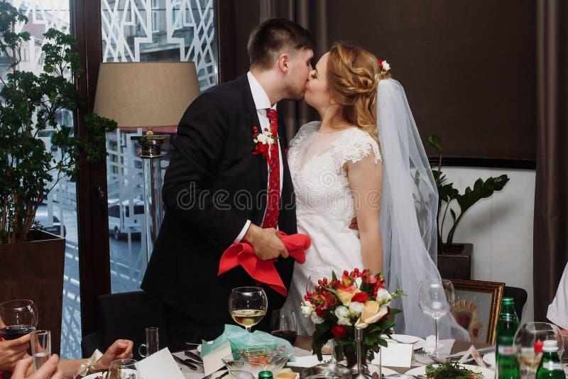 Jungvermähltenpaare, die am Hochzeitsempfang im Restaurant, brid küssen lizenzfreie stockfotos