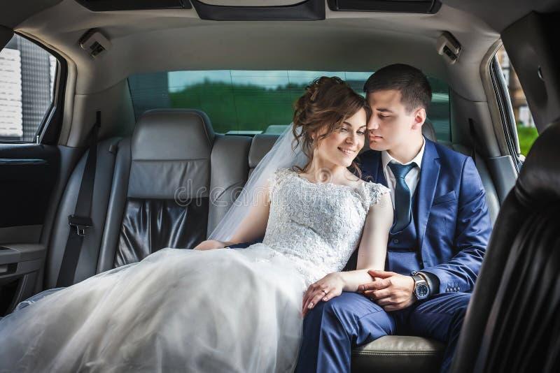 Jungvermähltenpaare, die im Auto umarmen stockfotografie