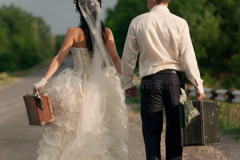 Jungvermähltenpaare, die Koffer Bargeld anhalten stockfoto