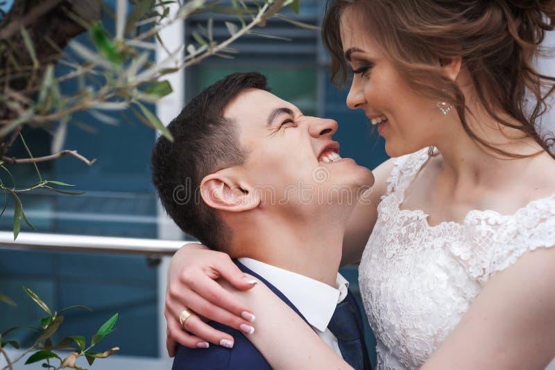 Jungvermähltenpaare, die nahe Baum im Luxusrestaurant umarmen und lächeln stockfoto