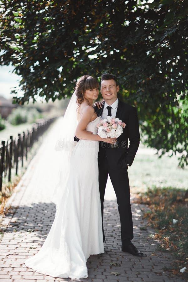 Jungverm?hlten des gl?cklichen Paars, Braut- und Br?utigamst?nde und halten Blumenstrau? von Blumen und von Gr?ns im Garten lizenzfreie stockfotos