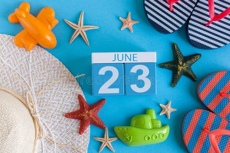 23 juni Beeld van 23 juni kalender op blauwe achtergrond met de zomerstrand, reizigersuitrusting en toebehoren Boom op gebied royalty-vrije stock foto's