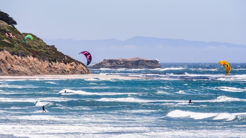 Juni 6, 2019 Davenport/CA/USA - folkdrake som surfar i Stilla havet, nära Santa Cruz, på en solig och varm dag royaltyfri fotografi