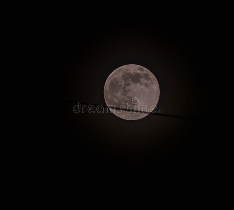 Juni fullmåne som omges av en gloria som orsakas av gaser i atmosen royaltyfria bilder