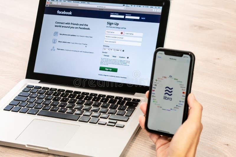 18 Juni 2019, Ljubljana Slovenien - hand som rymmer en smartphone med Våglogo på den och Vågs partners, bredvid fotografering för bildbyråer