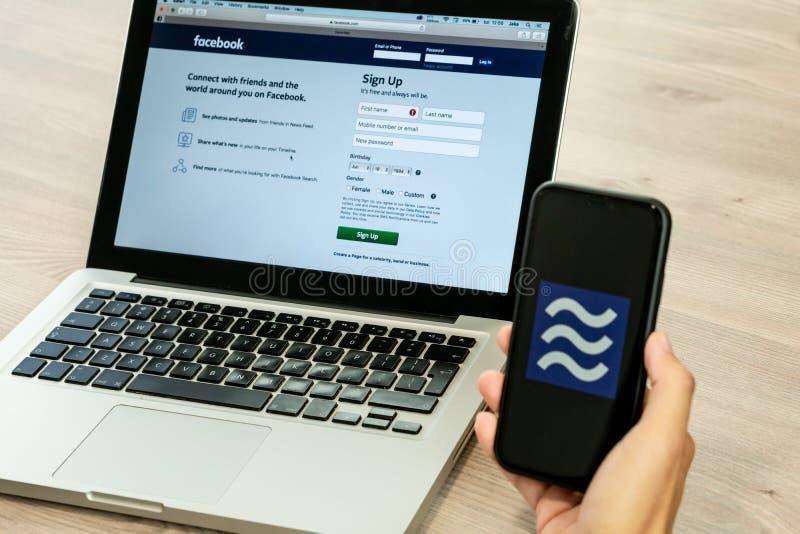 18 Juni 2019, Ljubljana Slovenien - handen som rymmer en smartphone med Våglogo på den, bredvid den Facebook websiten, öppnade på arkivbild