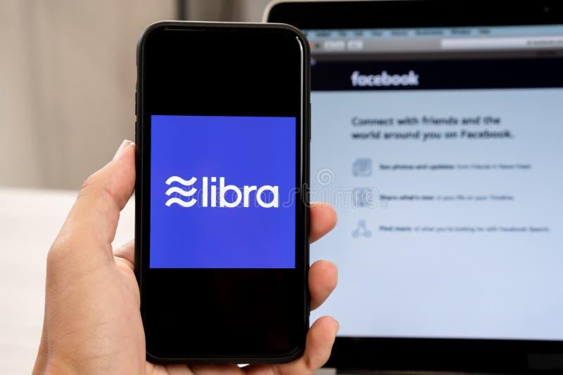 18 Juni 2019, Ljubljana Slovenien - handen som rymmer en smartphone med Våglogo på den, bredvid den Facebook websiten, öppnade på arkivfoto